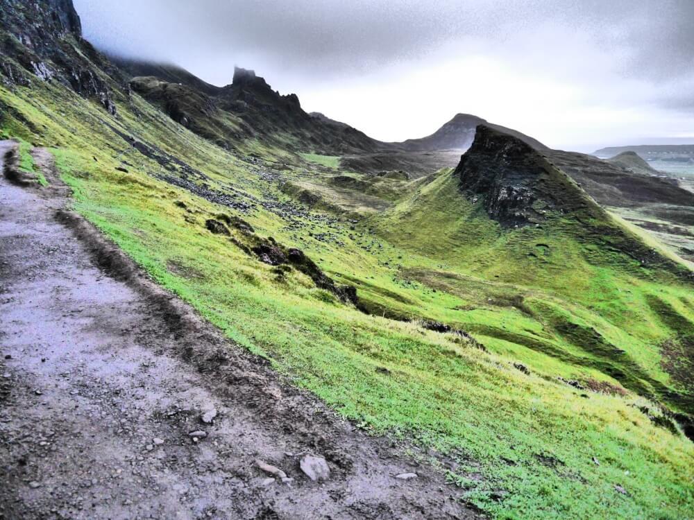 Matschiger Wanderweg neben grüner Landschaft